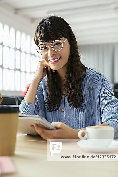 Portrait of smiling young woman with notepad at desk in office