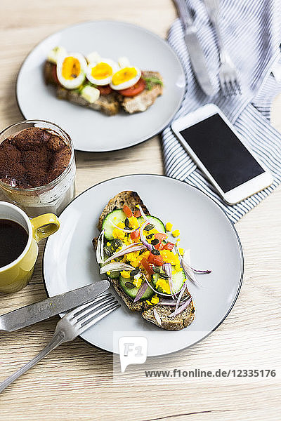 Vegetarian breakfast with bread  eggs and cucumber slices on plate  smartphone  latte macchiato  coffee cup