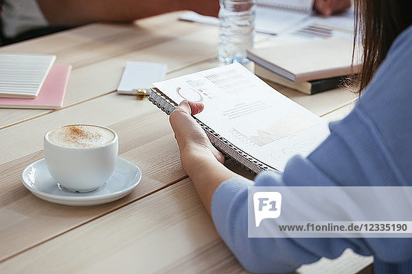 Woman working on paper at desk in office