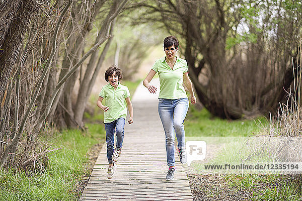 Happy mother and daughter running on boardwalk