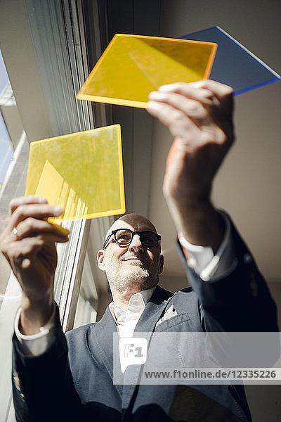 Senior architect standing at window  choosing materials