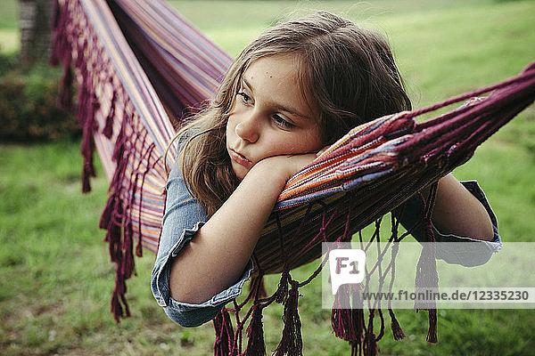 Portrait of sad girl lying in hammock