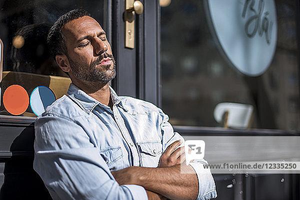Relaxed man outside a cafe enjoying the sunshine