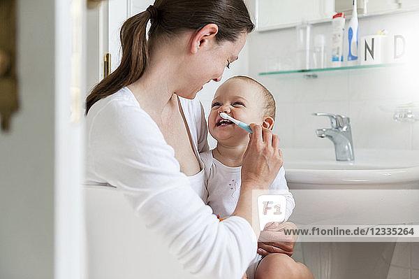 Mother brushing baby's teeth in bathroom