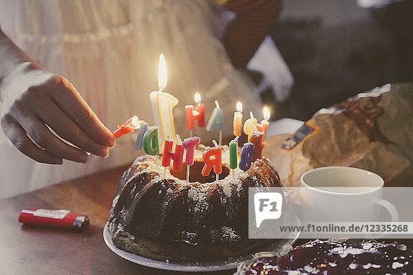 Woman lightning birthday cake candles  partial view