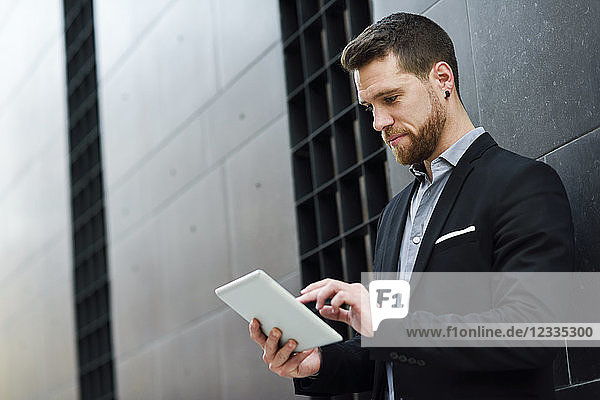 Young businessman looking at his digital tablet