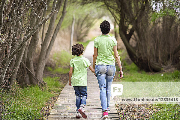 Rear view of mother and daughter walking hand in hand on boardwalk