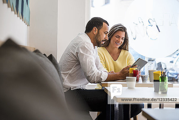 Young woman and man sharing tablet in a cafe
