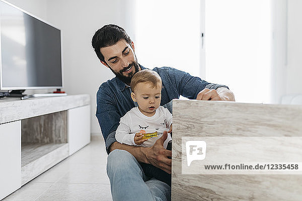 Father and daughter assembling a wooden table at home