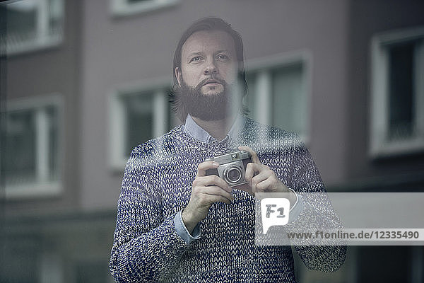 Man with beard taking pictures with old camera