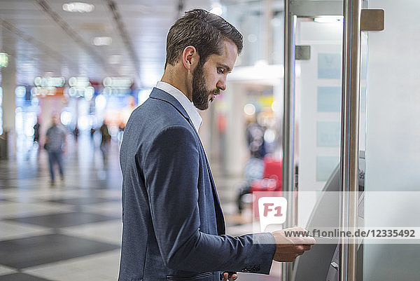 Young businessman withdrawing money at an ATM in the city