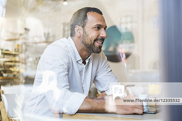 Smiling man with tablet in a cafe