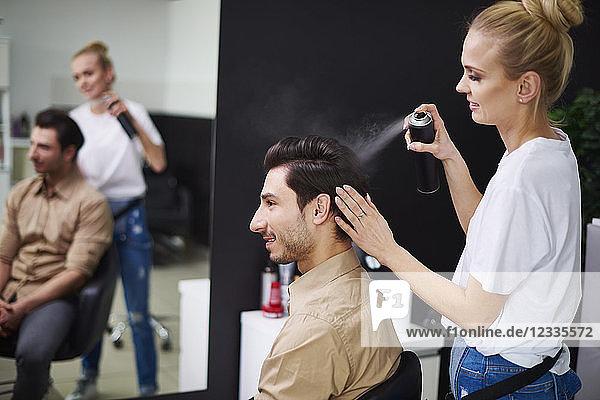 Smiling hairdresser using hairspray on man's hair
