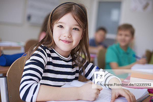 Portrait of smiling schoolgirl writing in exercise book in class