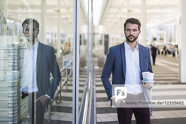 Young businessman holding tray with takeaway coffee
