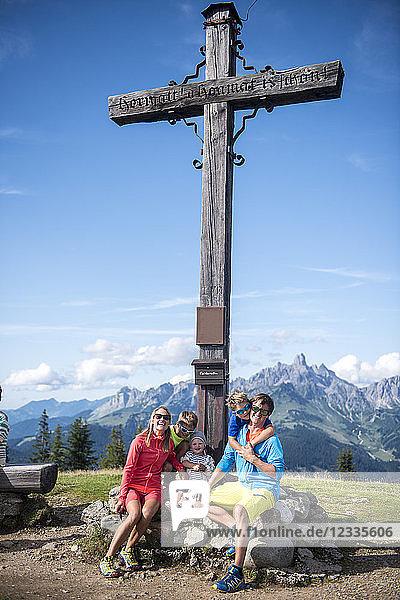 Austria  Salzburg State  Untertauern  family sitting at summit cross