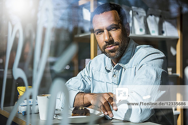 Portrait of man with piece of cake in a cafe