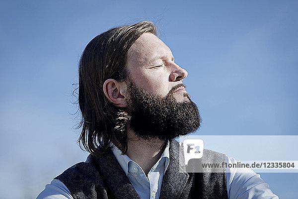Portrait of bearded man enjoying sunlight