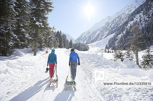 Couple with sledge walking in snow-covered landscape