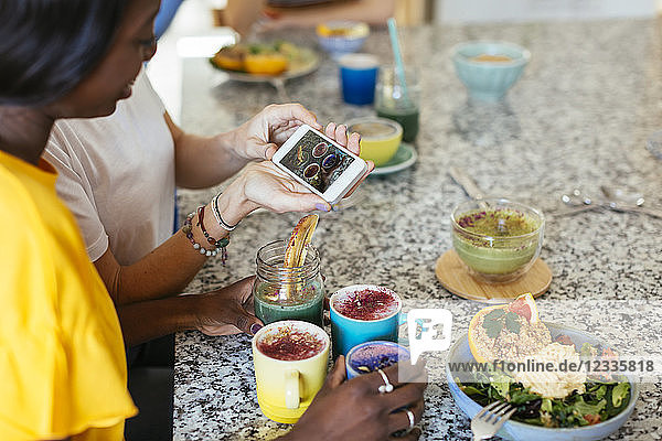 Woman showing smartphone picture in a cooking workshop
