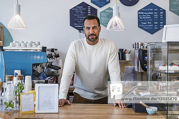 Portrait of confident owner behind the counter of a cafe