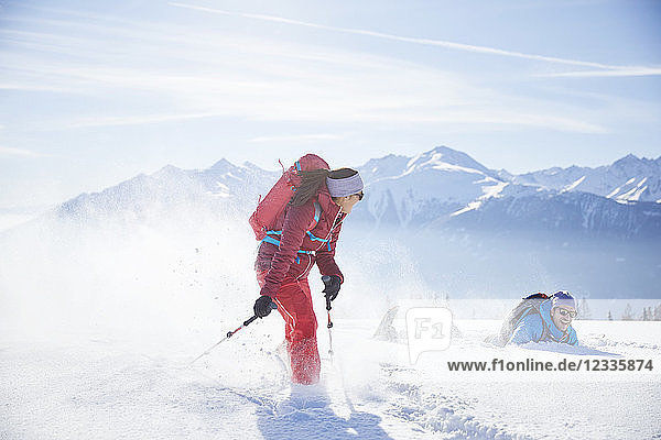 Austria  Tyrol  snowshoe hikers running through snow  man falling
