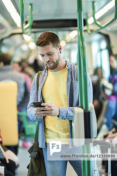 Young man in a subway train looking at his smartphone