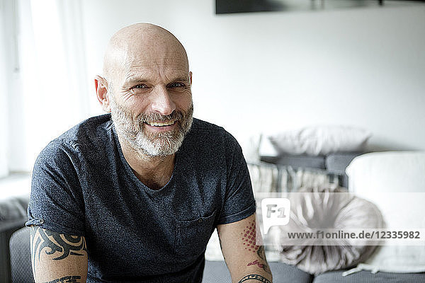 Tattooed man at home sitting on couch