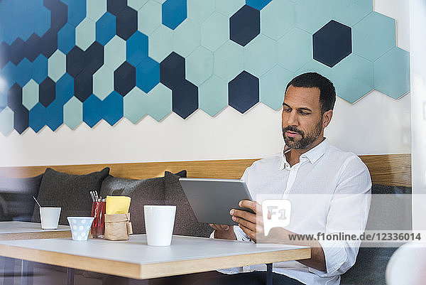 Man using tablet in a cafe