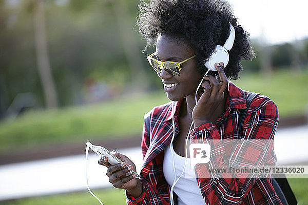 Portrait of happy young woman listening music with headphones and smartphone