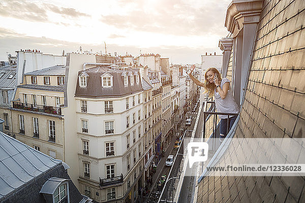 France  Paris  waving woman on the phone standing on balcony looking down