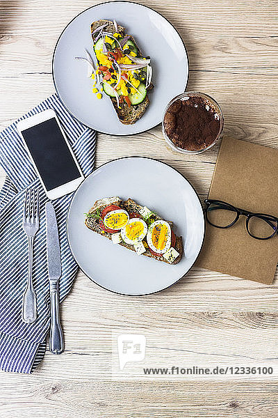 Vegetarian breakfast with bread  eggs and tomato slices on plate  latte macchiato  smartphone  notebook