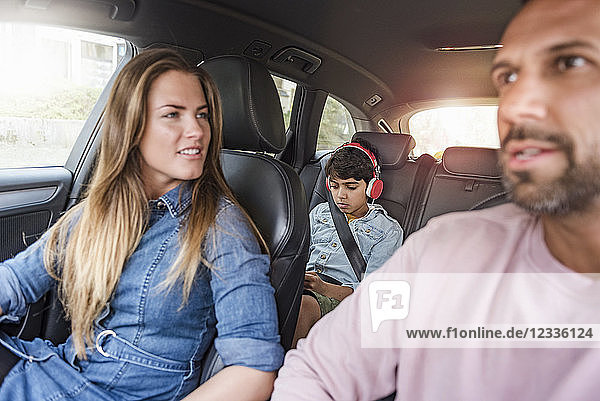 Family on a road trip with boy wearing headphones