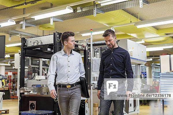 Two men talking in factory