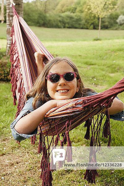Portrait of smiling girl wearing sunglasses lying in hammock
