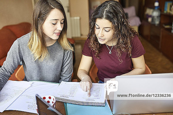 Two female students at desk working and learning together