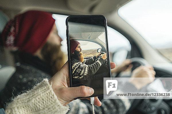 Iceland  woman taking photo of her boyfriend driving van