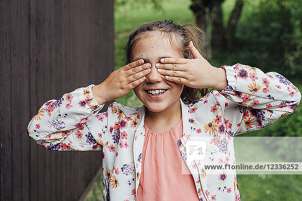 Portrait of smiling girl covering eyes with her hands