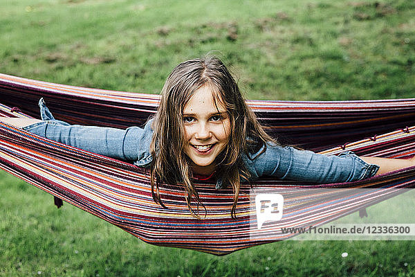 Portrait of smiling girl lying in hammock sticking out tongue