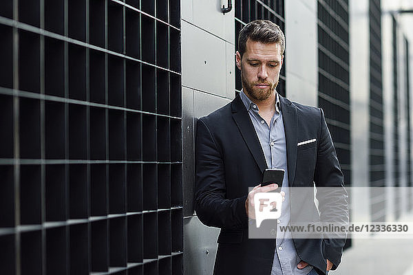 Young businessman looking at his smartphone