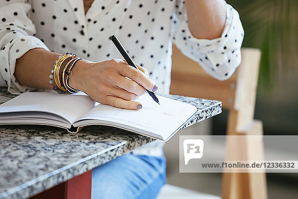 Close-up of woman writing in notebook on table