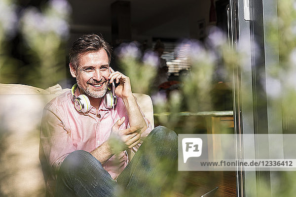 Smiling mature man on the phone sitting at open terrace door