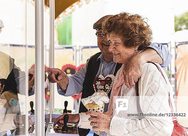 Senior couple having fun with gaming machine on fair