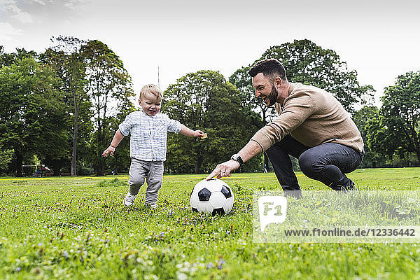 Happy father playing football with son in a park