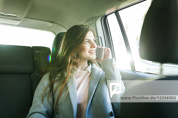 Smiling young businesswoman on the phone sitting on backseat of a car looking out of window
