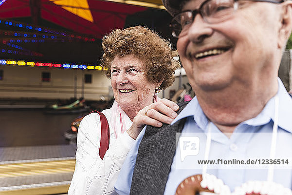 Portrait of senior woman having fun together with her husband on fair