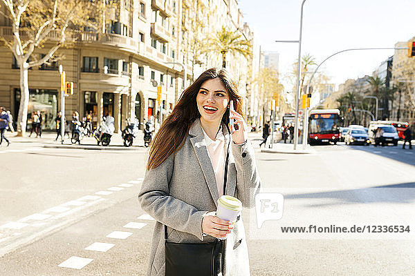 Spain  Barcelona  portrait of smiling young woman on the phone standing at roadside