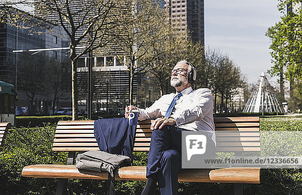 Mature businessman sitting on a bench listening to music