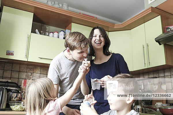 Boy opening surprise egg  daughter feeding father with chocolate  mother laughing