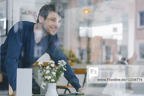 Smiling man in a cafe looking out of window